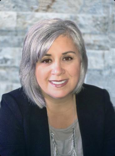 Lorrie Matarazzo, Au.D., Docteure en Audiologie, qui sourit devant un arrière-plan de brique grise